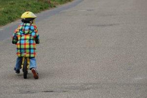 Ein kleines Kind auf einem Laufrad aus Holz.